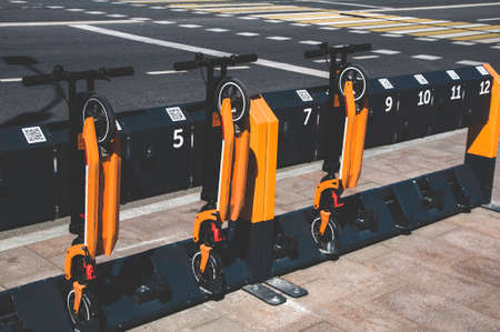 Electric scooters in row on the parking lot. City bike rental system concept