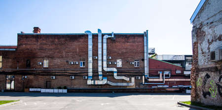 Ventilation or air conditioning pipes on the facade of a red brick building Stockfoto