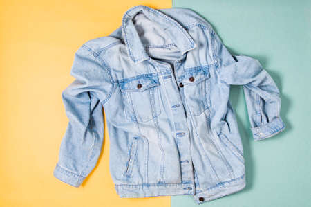 Blue denim jacket on yellow green background. Flat lay and top view