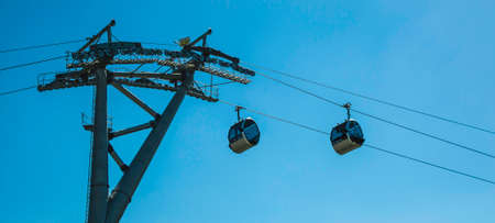 Cable car with cabins on background of blue sky Фото со стока