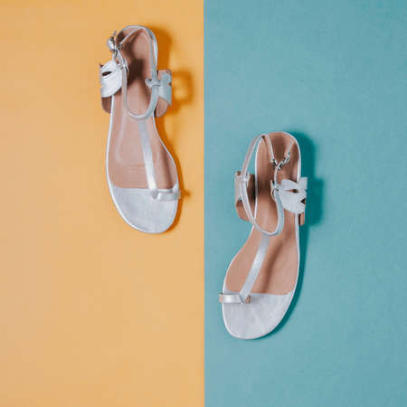 Silver womens sandals on a yellow-green background. Flat lay and top view