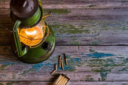 Old oil lamp, matches and a compass on a wooden background