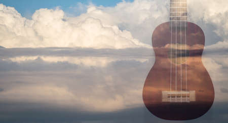 Double exposure with Ukulele and clouds background. Music or arts concept