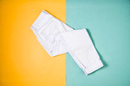 Light jeans on yellow green background. Flat lay and top view 写真素材