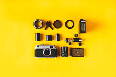 Old camera and photo accessories on yellow background. Flat lay and top view Stockfoto