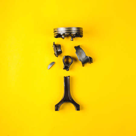 Old broken piston and connecting rod on yellow background