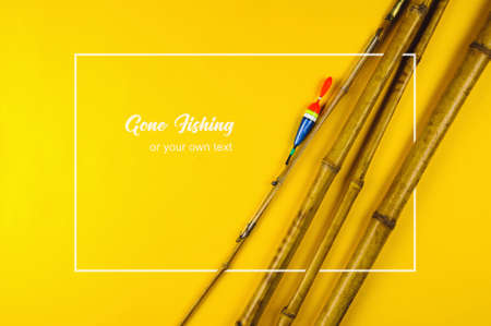 Old bamboo fishing rod on yellow background