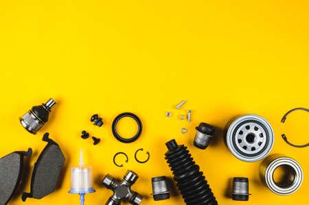 Conjunto de piezas de automóvil para mantenimiento sobre fondo amarillo Foto de archivo