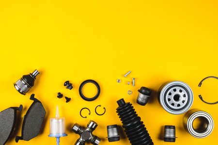 Set of car parts for maintenance on yellow background Archivio Fotografico