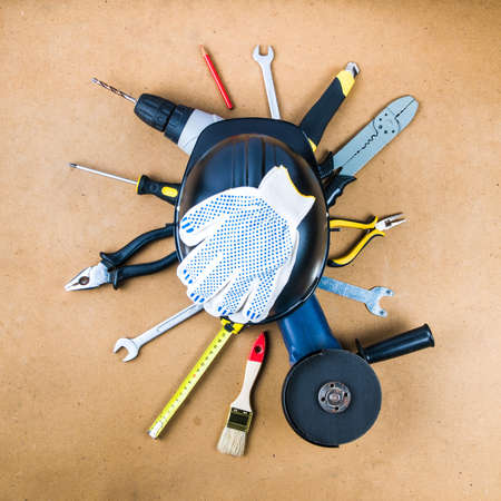 Black helmet and modern tools on the background of hardboard