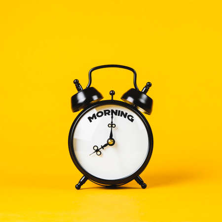 Vintage alarm clock and text Morning on it on yellow background