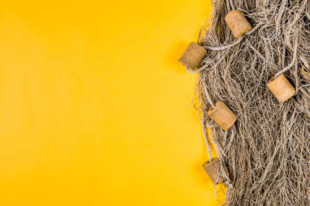 Old fishing net on yellow background. Space for text or design