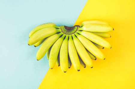 Banana isolated on turquoise-yellow background. Flat lay and top view