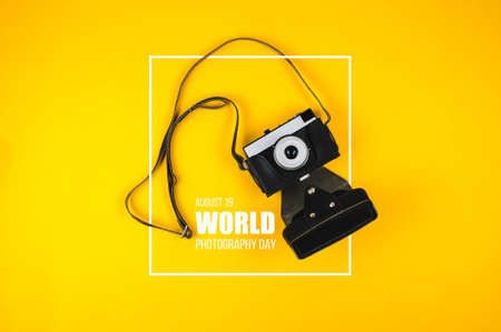 Old camera and text World photography day on yellow background