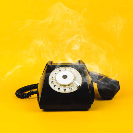 Old phone and smoke on yellow background
