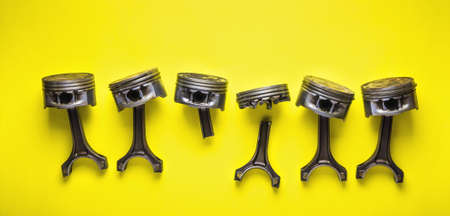 Old broken pistons and connecting rods on yellow background