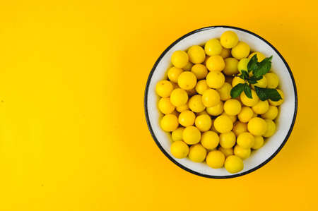 Yellow plums in white plate on yellow background Stockfoto