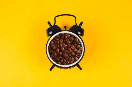 Collage of alarm clock and coffee beans on a yellow background Stockfoto
