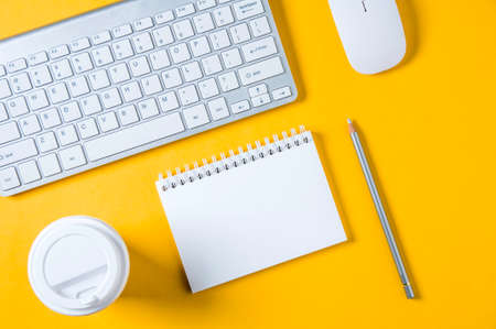 White keyboard, mouse and Notepad on yellow background. Flat lay and top view Imagens