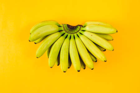 Banana isolated on yellow background. Flat lay and top view