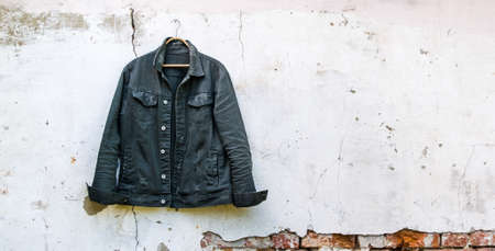 Mens denim jacket on the background of the old wall