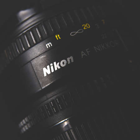 Russia, Moscow, October 02, 2019: Old lens with Nikon logo and Nikkor text on dark background