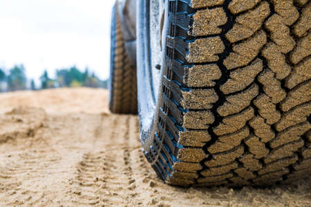 All-terrain tires in the sand close-up on a sandy road