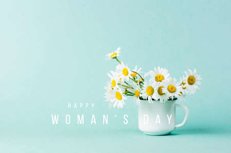 White daisy in white iron mug and the text Happy Womans Day on turquoise background Imagens