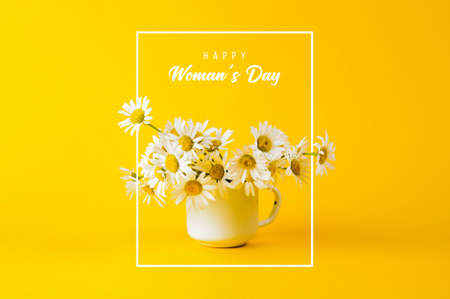 Daisy in white iron circle and the text Happy Womans Day on yellow background