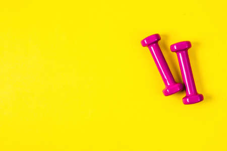 Pink dumbbells on an yellow background, a concept of sports or weight loss