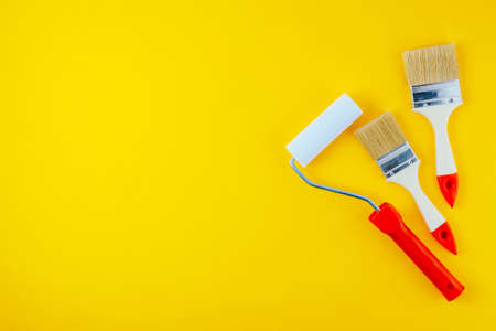 Paint brushes and roller on a yellow background. Space for text or design 写真素材