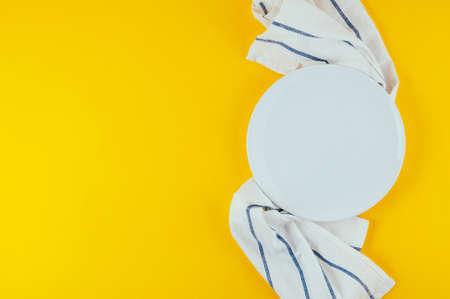 Kitchen textiles and white plate on bright yellow background