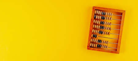 Old wooden abacus isolated on yellow background