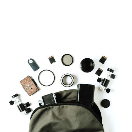 Old camera, green backpack and photo accessories on pale background