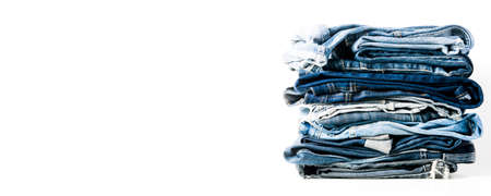 A stack of old jeans isolated on a light background
