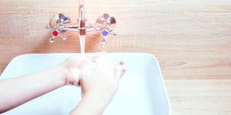 The child washes his hands with soap. Personal hygiene to stop spreading coronavirus Banco de Imagens