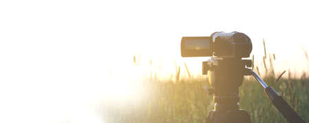 An old video camera on a tripod is set in a field with a sunset background