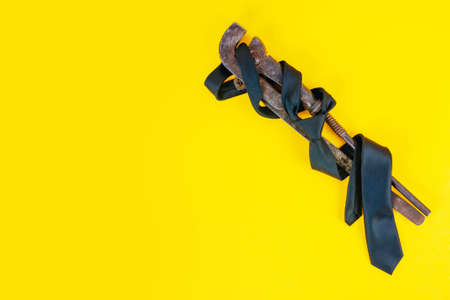 Fathers day concept. A rusty wrench and a black tie on a bright yellow background Banco de Imagens