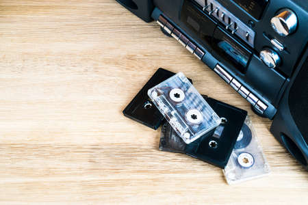 Old audio cassettes and a player on a wooden table Stockfoto