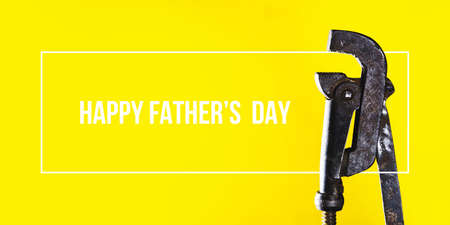 Fathers day concept. A rusty wrench on a bright yellow background