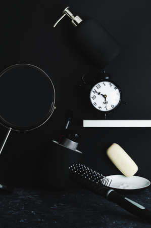 Morning hygiene supplies are scattered in disarray on a black background. The concept of the morning hustle and bustle