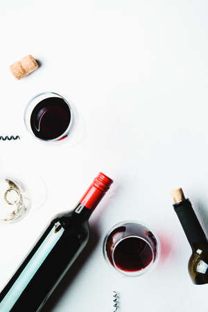 Glasses of red and white wine and bottles on a white concrete background. Flat lay and top view, copy space for text or design 免版税图像