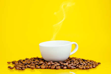 Coffee beans and a white Cup on a bright yellow background