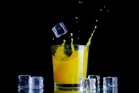 Splashes of orange juice in a clear glass with ice cubes on a dark background