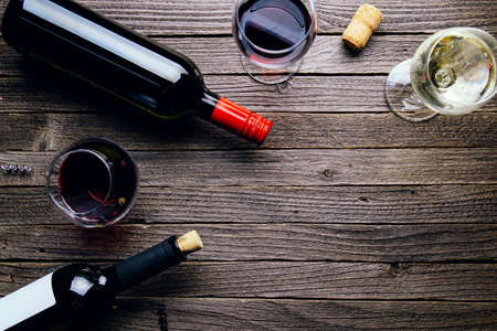 Glasses of red and white wine and bottles on a dark wooden background. Flat lay and top view, copy space for text or design