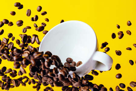 Flying coffee beans and a white Cup on a bright yellow background
