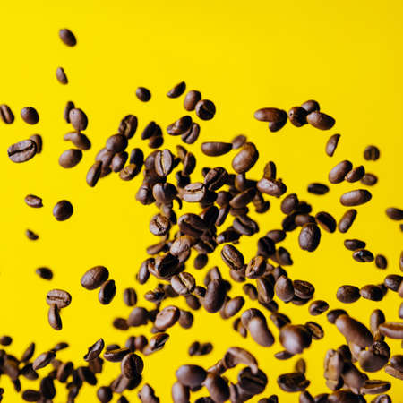 Flying coffee beans on a bright yellow background 免版税图像