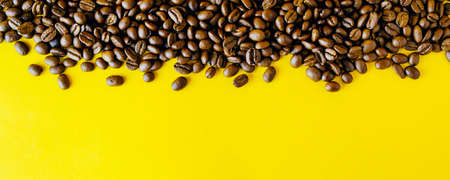 Сoffee beans on a bright yellow background. Copy space for text and panoramic frame