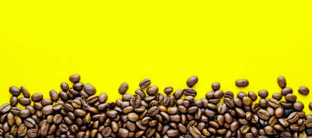 Ð¡offee beans on a bright yellow background. Copy space for text and panoramic frame