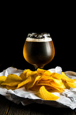 A glass of beer and potato chips on a wooden table and a dark background 免版税图像